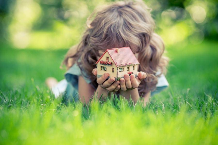 girl in grass holding little home