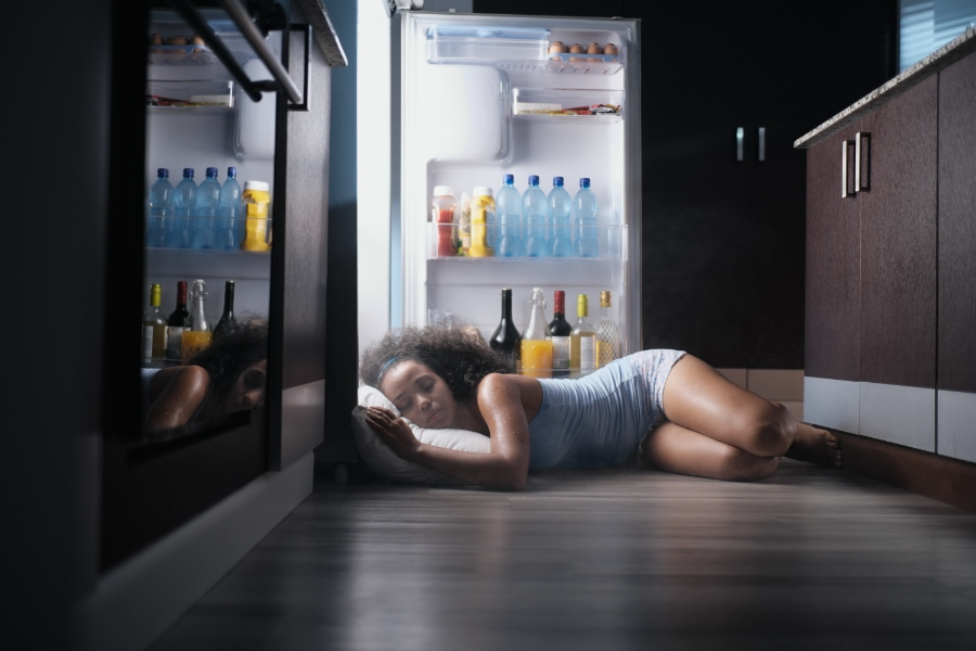 Woman sleeping by open refrigerator because she turned her AC off.