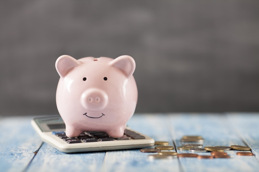 Piggy bank on top of calculator depicting saving money on energy costs.