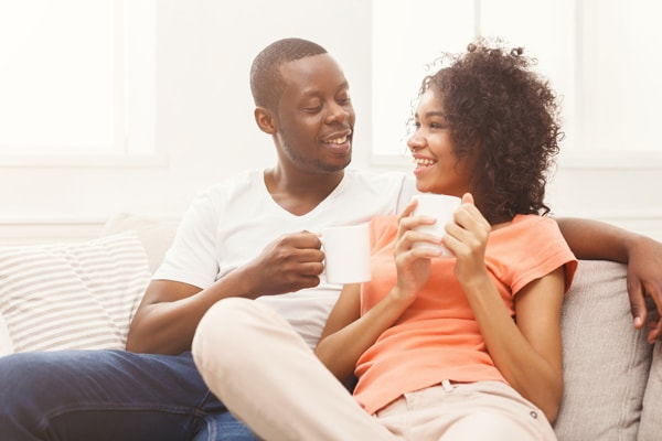 Happy african-american couple drinking coffee at cozy home.