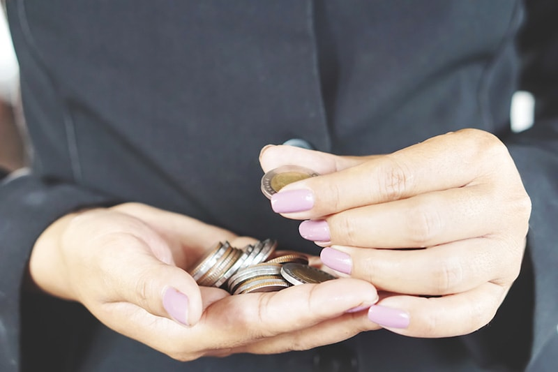 woman counting coins pink fingernails